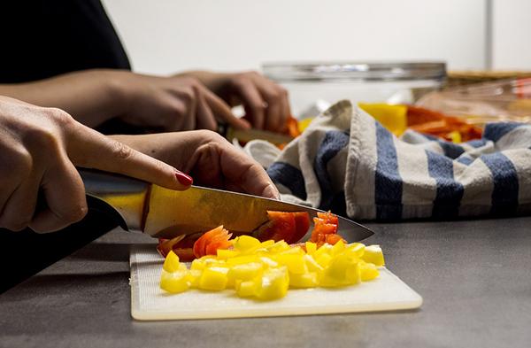 Mulher com faca a cortar legumes