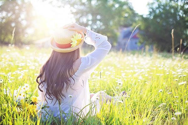 Mulher de chapéu sentada no campo