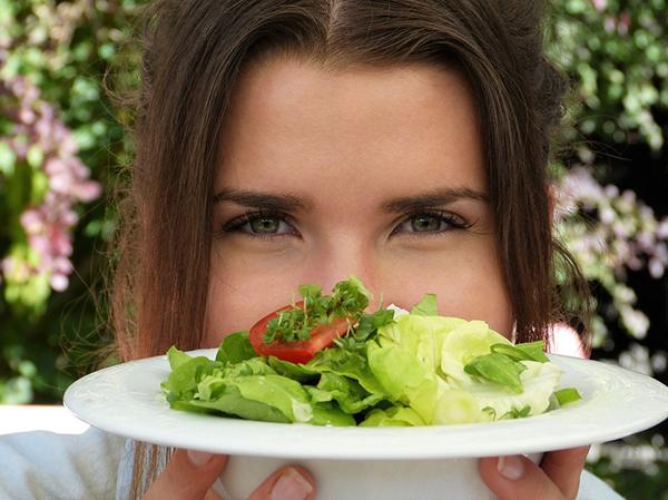 Mulher a segurar prato com salada