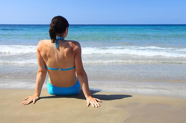 Mulher de costas sentada na praia à beira mar