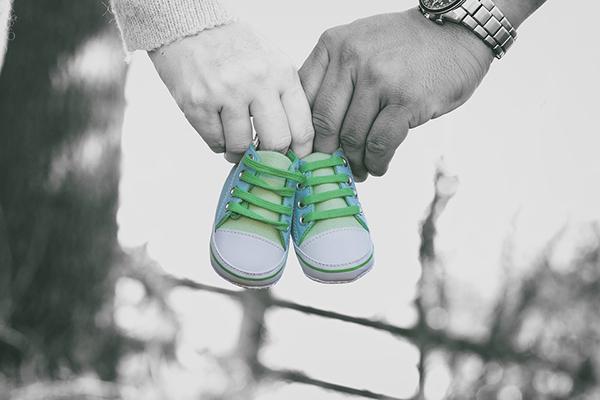 Casal a segurar e par de sapatos de bebé