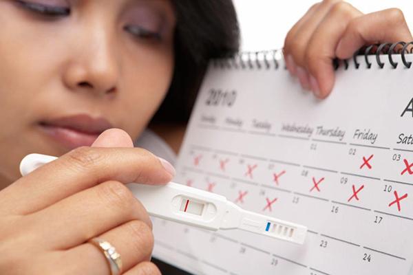 Mulher com teste de gravidez e calendário