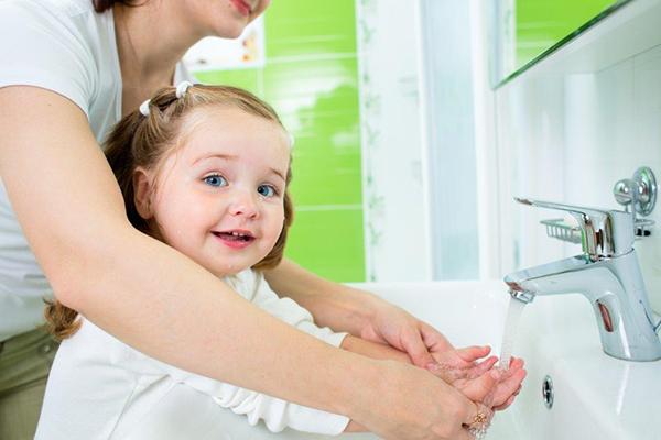 Mãe ajuda filha a lavar as mãos