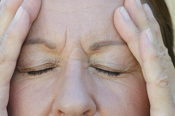 Mulher de olhos fechados com as mãos na cabeça