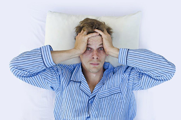 Homem deitado de pijama com insónias