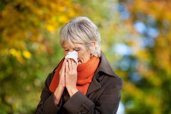 Mulher a espirrar devido a rinite alérgica