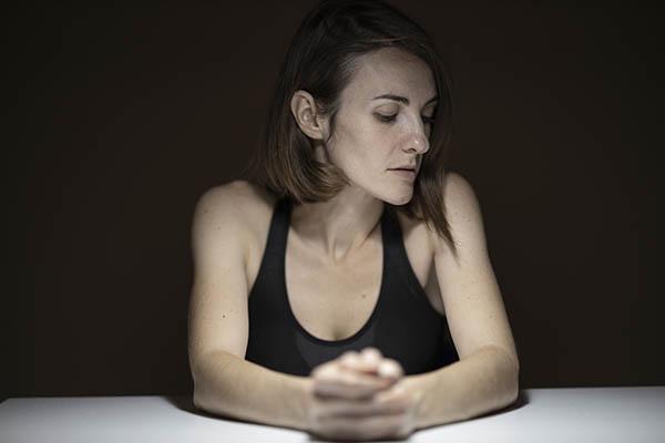 Mulher com ar preocupado sentada à mesa