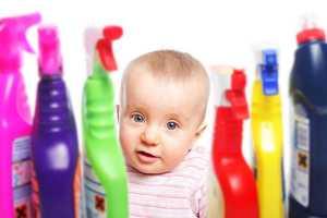 Bebé perto de frascos de detergente
