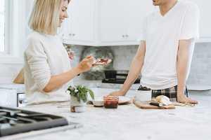 Mulher na cozinha a comer torrada com geleia