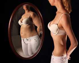 Mulher anorética a ver-se ao espelho