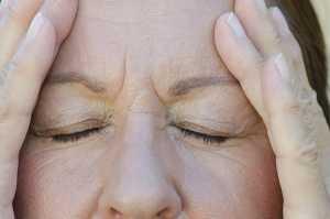 Mulher de olhos fechados com dor de cabeça