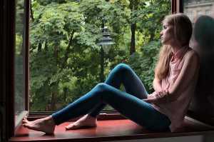 Rapariga triste sentada no parapeito de janela