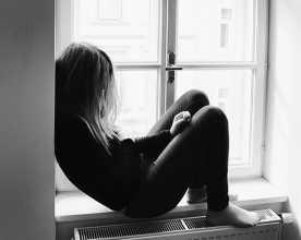 Adolescente depressiva sentada perto de janela