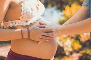 Grávida a segurar as mãos do marido na sua barriga