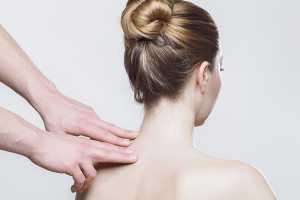 Fisioterapeuta com os dedos no pescoço de mulher