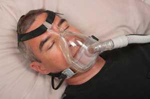 Homem a dormir com máscara para apneia do sono