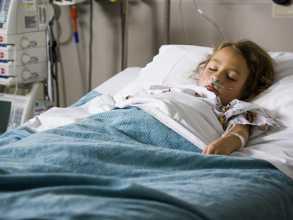 Criança internada em cama de hospital