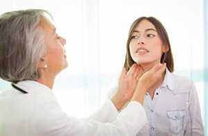 Médica faz palpação da tiroide em mulher jovem