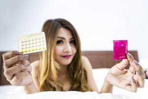 Mulher a segurar em preservativo e embalagem de pílula