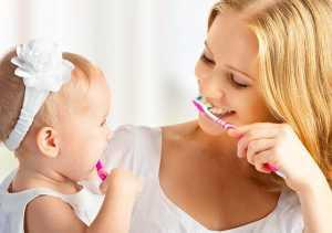 Mãe ensina filha a lavar os dentes