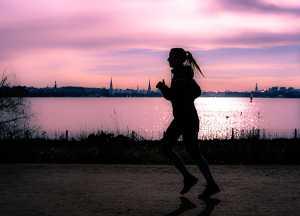 Mulher a fazer jogging junto a lago