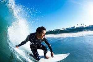 Homem a fazer surf para ilustrar as exostoses ou ouvido de surfista