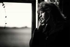 Mulher à janela com ar triste