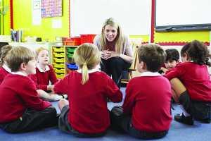 Educadora e crianças sentadas no chão