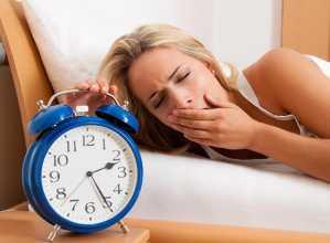 Mulher na cama a bocejar ao lado de relógio