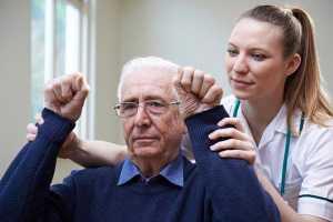 Mulher fisioterapeuta ajuda idoso a fazer exercícios