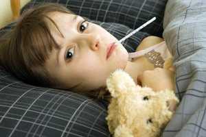 Criança deitada a medir a febre com termómetro na boca