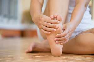 Mulher descalça com dor no pé