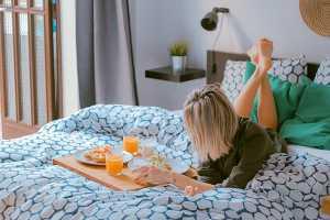 Mulher deitada na cama a tomar pequeno almoço
