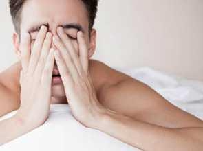 Homem na cama com insónia ou dificuldade em dormir