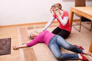 Mulher ao telemóvel a prestar auxílio a mulher desmaiada no chão