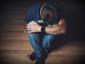 Homem sentado no chão com a cabeça apoiada nos joelhos