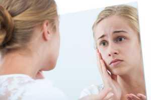 Mulher com ar preocupado vê-se ao espelho