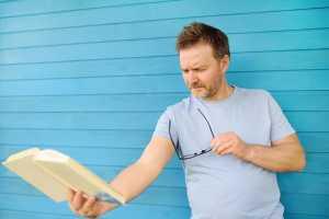 Homem com dificuldade visual para ler livro