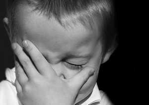 Criança a tapar um olho com a mão