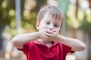 Rapaz a tapar a boca com as mãos