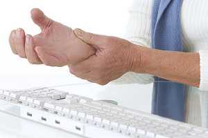 Homem ao computador com dor no pulso