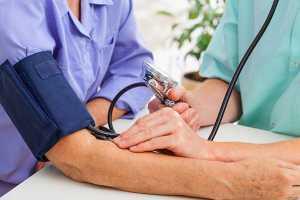 Médico a medir a tensão arterial