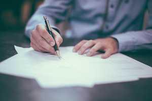 Homem a assinar documento