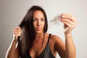 Mulher com bocado de cabelo na mão