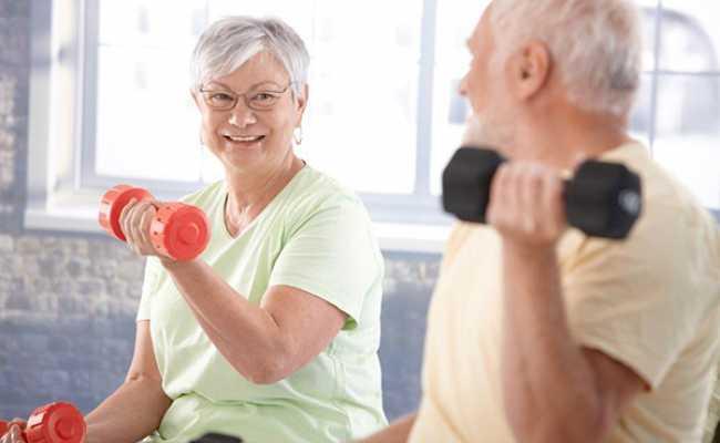 Casal de idosos a fazer exercício com pesos