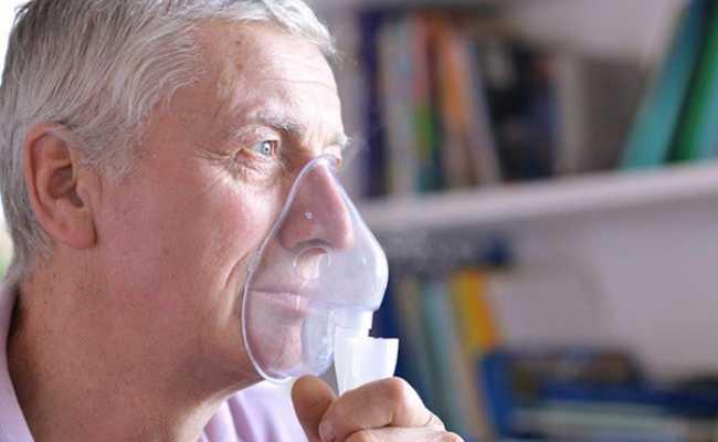 Homem de cabelo grisalho com máscara de oxigénio