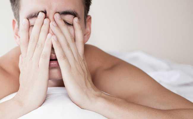 Homem na cama com as mãos na cara