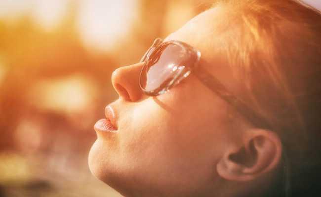 Mulher com óculos de sol a olhar para o céu